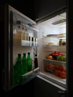 Refrigerator with open door, containing fruits and vegetables and bottled water